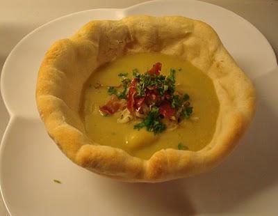 Cremet rodfrugtsuppe med serranoskine og porrer, serveret i brødskåle